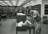 Soldier looking at the new books in the Post Library, Building 4679